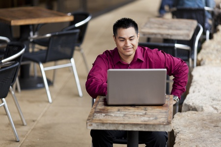 telecommuting: Stock photo of a well dressed Hispanic businessman looking down at a laptop while telecommuting from an internet cafe. Stock Photo