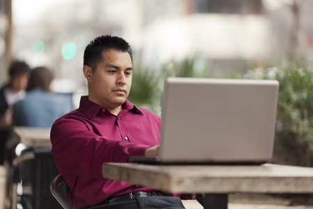 telecommuting: Stock photo of a Hispanic businessman looking down at his laptop computer while telecommuting at an internet cafe.