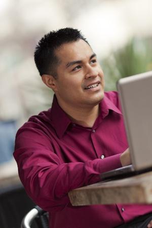 cafe internet: Foto de archivo de un feliz hombre de negocios hispana mirando a su ordenador port�til, mientras que el teletrabajo en un caf� Internet.