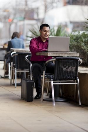 internet cafe: Foto de archivo de un hombre de negocios bien vestidos hispana mirando hacia abajo en un ordenador port�til, mientras que el teletrabajo desde un caf� Internet. Foto de archivo