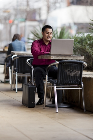 Stock photo of a well dressed Hispanic businessman looking down at a laptop while telecommuting from an internet cafe. Stock Photo