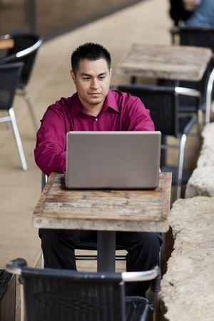 cafe internet: Foto de archivo de un hombre de negocios bien vestidos hispana mirando hacia abajo en un ordenador port�til, mientras que el teletrabajo desde un caf� Internet. Foto de archivo
