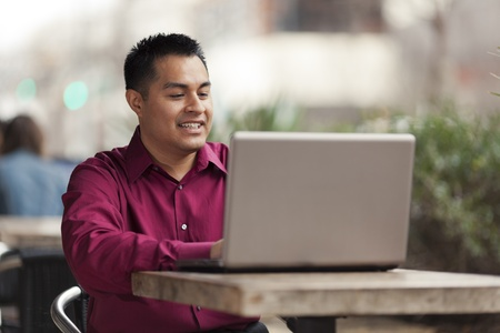Stock photo of a happy Hispanic businessman looking down at his laptop computer while telecommuting at an internet cafe.