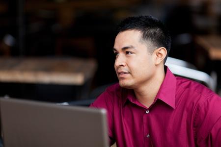 cafe internet: Foto de archivo de un hombre de negocios bien vestidos, quienes trabajan con un ordenador port�til, mientras que el teletrabajo desde un caf� Internet.