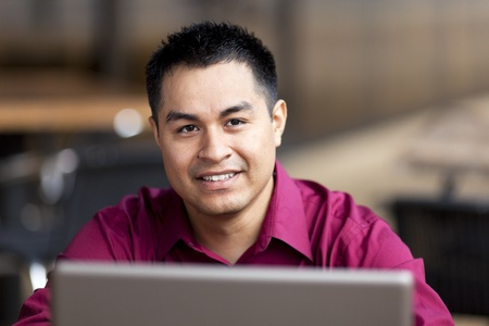 Stock photo of a well dressed Hispanic businessman looking up from a laptop while telecommuting from an internet cafe.