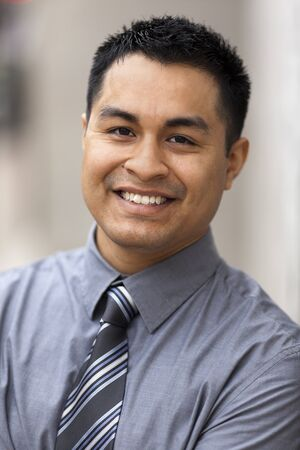 Stock closeup headshot photo of a smiling Hispanic businessman. Stock Photo