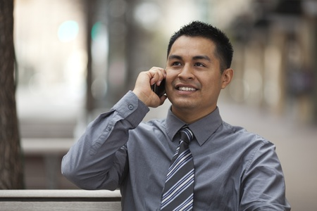 Stock photo of a Hispanic businessman sitting on a city bench and chatting on a cell phone with a happy expression. Stock Photo - 12746382