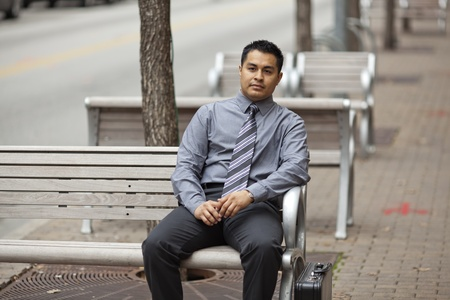Stock photo of a Hispanic businessman sitting on an bench in a business district with a briefcase. Stock Photo - 12746335