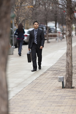 Stock photo of a well dressed Hispanic businessman carrying a briefcase while walking through a downtown business district. Stock Photo - 12746392