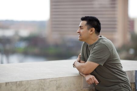 Stock photo of a casually dressed Hispanic man looking out from a stone balcony. photo