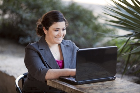 telecommuting: Stock photo of a well dressed businesswoman looking down at a laptop while telecommuting from an internet cafe.