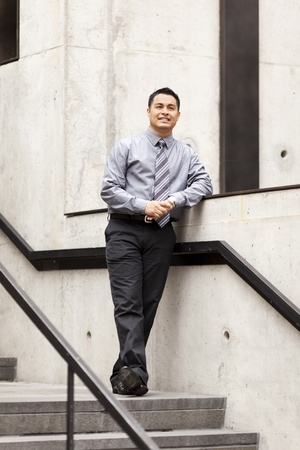 Stock photo of a Hispanic businessman leanging against a wall running alongside a stairwell. Stock Photo - 12746492