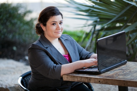 telecommuting: Stock photo of a well dressed businesswoman looking up at the camera and smiling as she works on a laptop while telecommuting from an internet cafe.