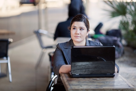 telecommuting: Stock photo of a well dressed businesswoman looking up from her laptop while telecommuting from an internet cafe.