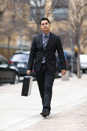 hair tie: Stock photo of a well dressed Hispanic businessman carrying a briefcase while walking through a downtown business district.