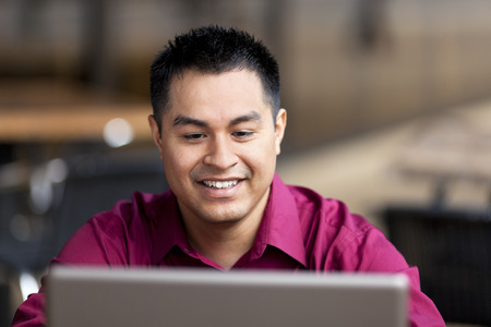 telecommuting: Stock photo of a well dressed Hispanic businessman looking down at a laptop while telecommuting from an internet cafe  Stock Photo