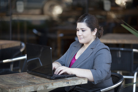 Stock photo of a well dressed businesswoman looking down at a laptop while telecommuting from an internet cafe  Banco de Imagens