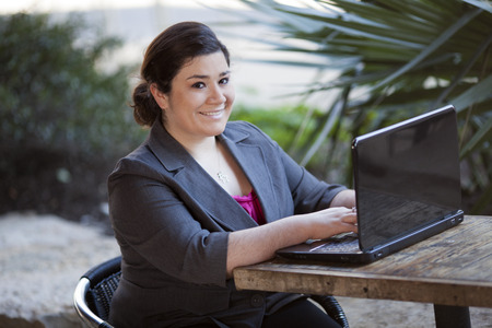 telecommuting: Stock photo of a well dressed businesswoman looking up at the camera and smiling as she works on a laptop while telecommuting from an internet cafe  Stock Photo