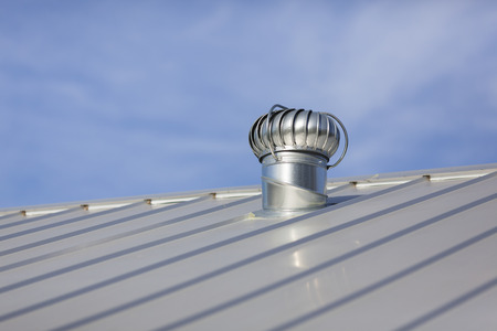 attic: Stock photo of an attic vent on a freshly installed, brand new metal roof at a residential home.