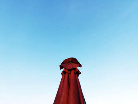 Red umbrella with blue sky background in ladies concept.If you try to imagine this image, then it is similar to a woman standing in red dress.