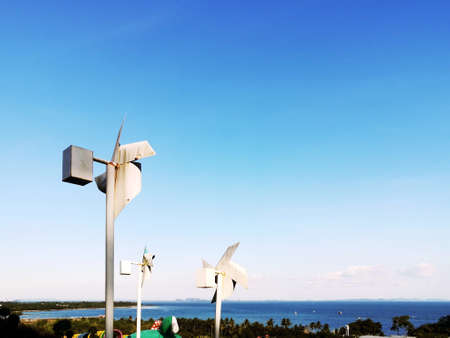 Wind turbines generating electricity and beautiful blue sky - Clean Energy and Renewable Energy Concepts.You can also see the beauty of the vast sea.