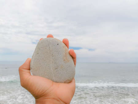 Stone texture.Hand holding a rock with sea background image.