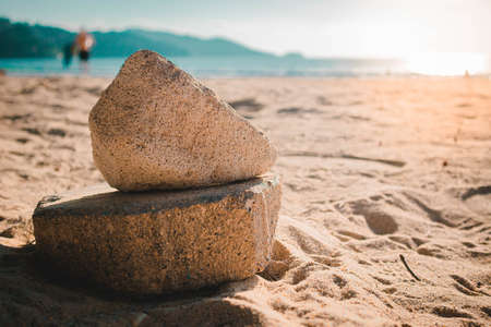 Stone on the beautiful sandy beach with a peaceful and relaxing summer holiday.