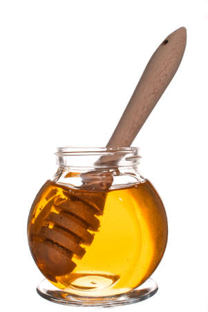 Jar of honey with wooden drizzler isolated on white background Imagens