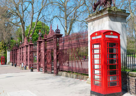 Two typical London bright red phone cabins infront big door photo
