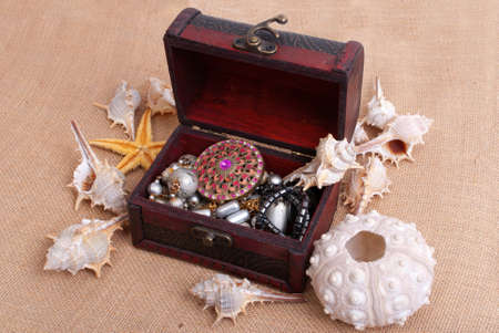 Box, shells and starfishes on sand background photo
