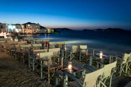 PAROS, GREECE, AUGUST 26: Cozy restaurant at night in Naussa, Paros on August 26, 2014. The beautiful picturesque fishing village of Naoussa is located in a huge bay in Paros island. photo