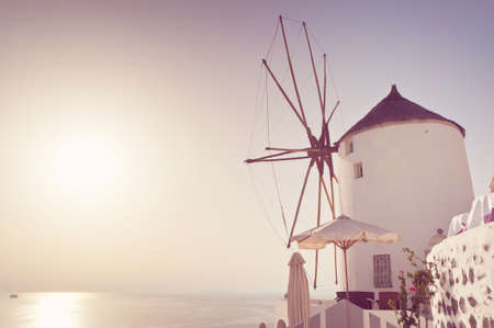 Windmill in Oia, Santorini. Oia is a village in the north west edge of the Santorini island with white houses, narrow streets and amazing seaviews. Stock Photo