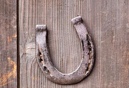 Horseshoe for luck on old wooden door Imagens