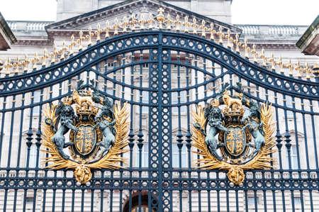 LONDON - königliches Wappen am Buckingham Palace Tor - berühmter Markstein, errichtet im Jahre 1705, Palast ist offizielle London-Wohnsitz und Hauptarbeitsplatz des britischen Monarchen. Standard-Bild - 86500476
