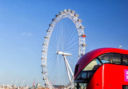LONDON, UK - JANUARY 2, 2015: The London Eye and iconic red bus. London Eye (135 m tall, diameter of 120 m), a famous tourist attraction over river Thames