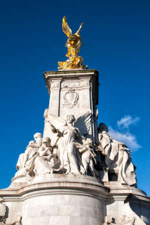 The Victoria Memorial is a sculpture dedicated to Queen Victoria, sculpted by Sir Thomas Brock in London, placed at the centre of Queens Gardens in front of Buckingham Palace.