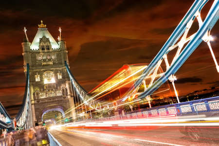 Tower Bridge in London, UK at night with moving red double-decker bus leaving light traces