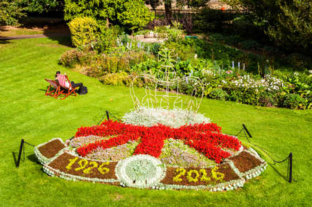 Bath, UK - September 22, 2014: Tourists and locals enjoy a sunny day in Parade Gardens. The Somerset city of Bath has UNESCO World Heritage status and receives over 4 million visitors each year Editorial