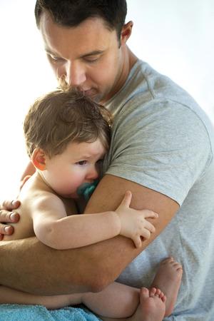 아기 소년 그의 아버지에 의해 위로되는