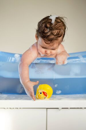 bathtime: Baby boy reaching for his rubber duck whilst sitting in the bath