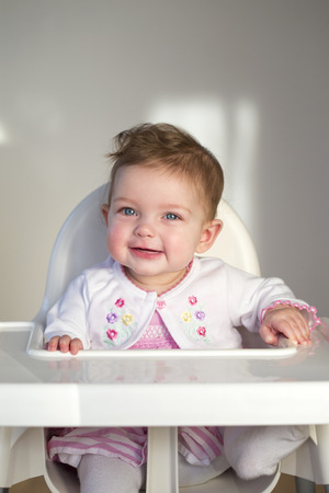 high chair: Baby girl looking happy sitting in her high chair