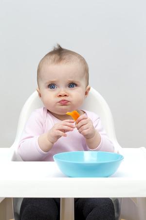 높은 의자에 그녀의 저녁 식사를 즐기는 아기 소녀
