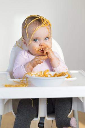 어린 소녀 그녀의 저녁 식사를 먹고 엉망으로 만드는