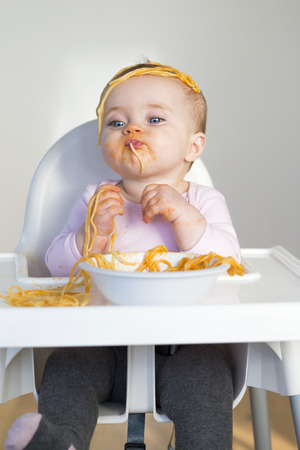 mess: Little Girl Eating her dinner and making a mess Stock Photo