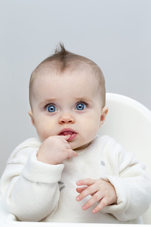 highchair: Little baby Girl sat in a highchair looking at camera. Stock Photo