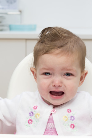 blue eyes girl: Baby girl sitting in a high chair and crying.