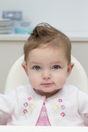 high chair: Close up image of a baby girl in a high chair