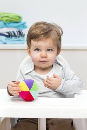 high chair: Baby boy sitting in a high chair with a toy ball. Stock Photo