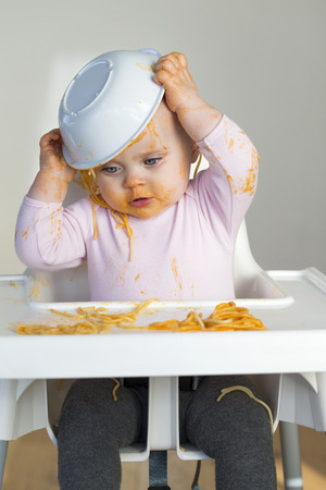 bebes lindos: Ni�a que come la cena y hacer un desastre. Foto de archivo