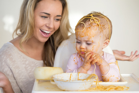 parents with one child: Young mother laughing at her baby daughter who has managed to get more of her food on her head than in her mouth. Stock Photo